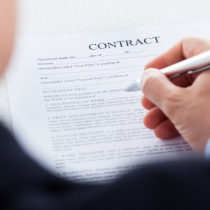 Hand holding pen over contract
