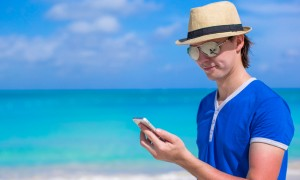 Man with his phone on beach