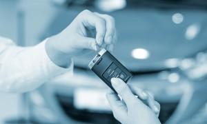 Salesman hands over car key to buyer