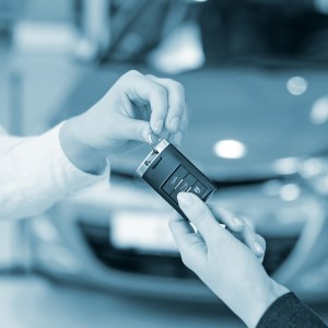 Salesman hands over car key to buyer