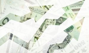 Saudi riyal bank notes behind arrows