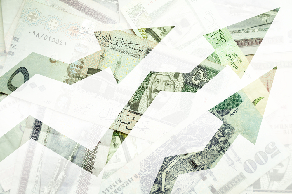 Saudi riyal bank notes behind arrows