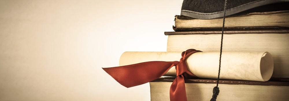 A graduation scroll on a stack of books