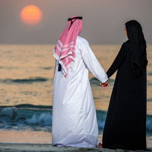 Arab couple at the beach watching the sunset