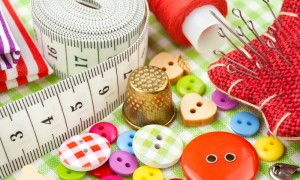 Sewing items buttons, fabrics, measuring tape, pin cushion