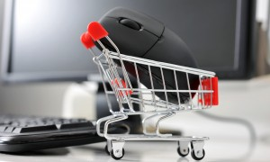 Shopping cart with mouse in front of computer.
