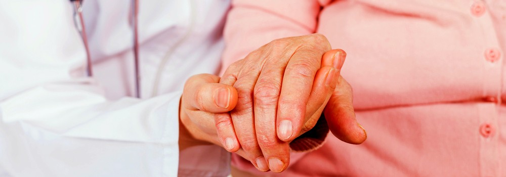 a doctor holding the hand of an old lady