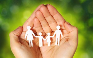 Hands hold paper-chain family