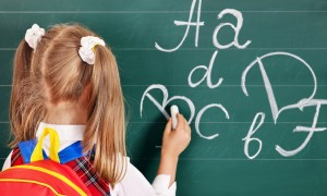 Girl writting on blackboard in school uniform