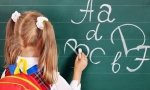 Girl writting on blackboard in school uniform