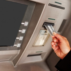 Person inserting a bank card into an ATM