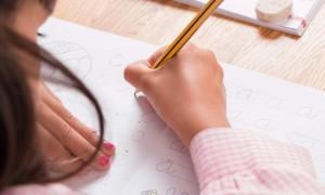 Schoolgirl in uniform writes in book