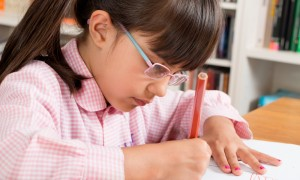 School girl in glasses and uniform works in book