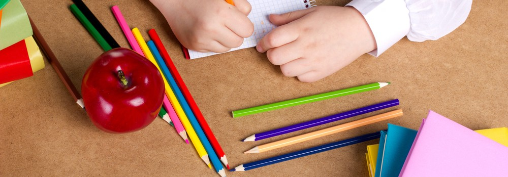 Child writes in school book, with apple and stationery on desk