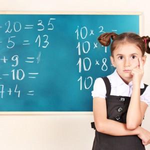 A girl standing near blackboard in the classroom