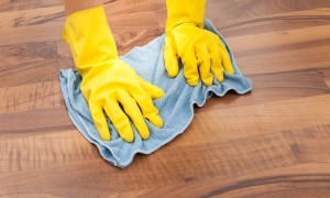 Maid in rubber gloves cleans wooden floor