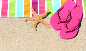 slippers kept next to a beach towel