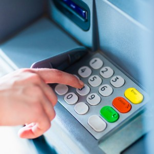 A hand entering PINpass code on an ATM