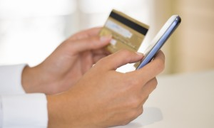 A person holding a credit card and using cell phone