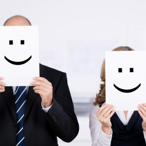 Businesspeople holding smileys on placard in front of faces at office