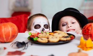 Two boys looking at cookies on Halloween table