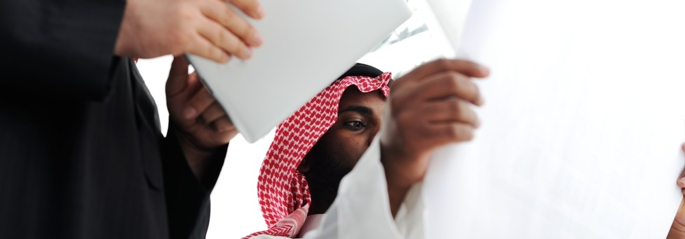 GCC businessmen work on tablet