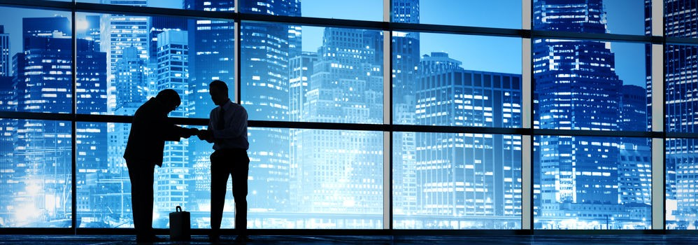 Businessmen in an empty office in front of skyscrapers at night