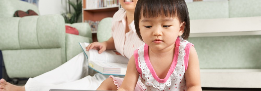 Little girl plays with mother or helper