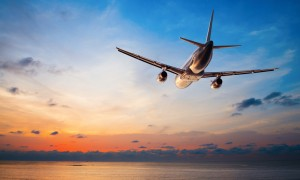 Aeroplane flies through sky at sunset