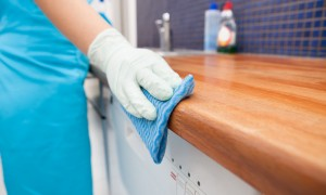 Woman in gloves cleans kitchen counter