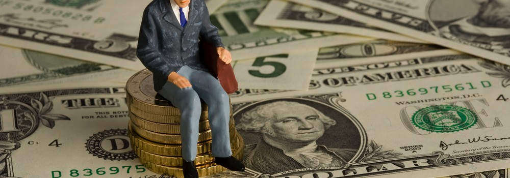 Pensioner toy sits on pile of coins and dollars