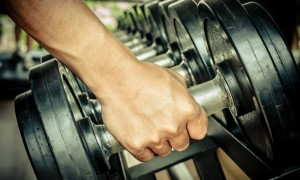 A man takes a heavy dumbbell in gym