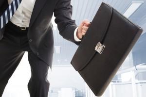 Briefcase held by running businessman