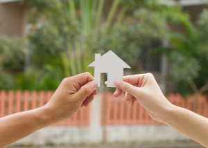 Young couple holding a white miniature house
