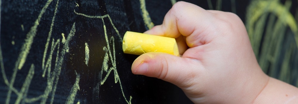 child draws with chalk on a blackboard