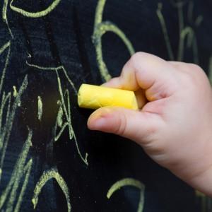 child draws with chalk on a blackboard