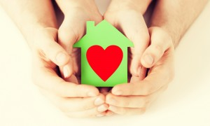 Closeup picture of male and female hands holding green paper house with red heart