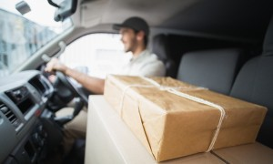 Delivery driver driving van with parcels on car seat
