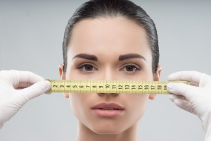 Woman face being measured by beautician hands, getting prepared for plastic surgery