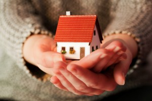 Woman holding a small new house in her hands