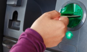 woman putting card in ATM machine