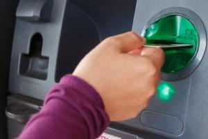 woman putting card in ATM machine