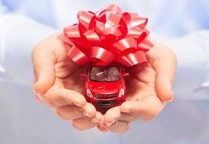 Close-up of a person holding a toy car in their hands