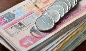 Dirham coins placed on stack of hundred dirham notes