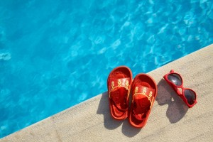 Colored sandal and sunglasses by the swimming pool