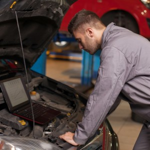 Mechanic looking on a computer connected to a car engine