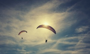 Two paragliders flies on background of sunset sky
