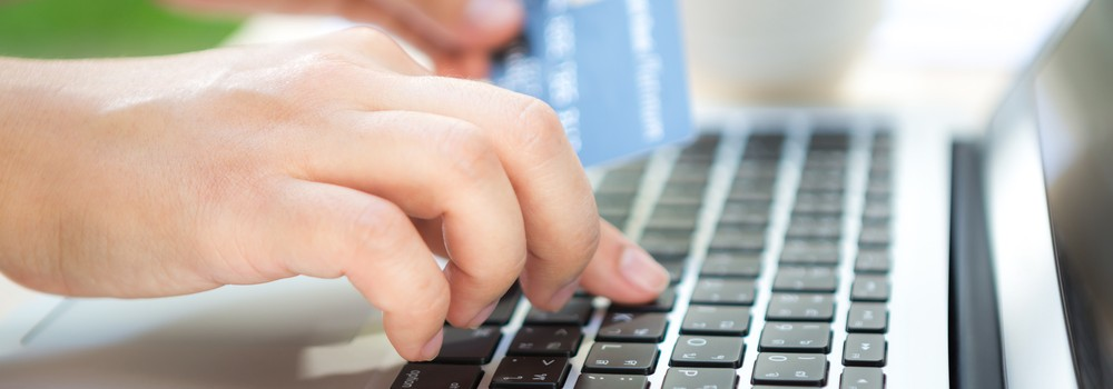 A person with credit card and using laptop computer for online shopping