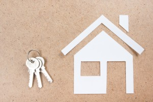 key with house figure and on wooden background