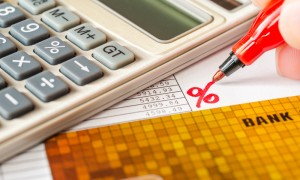 Calculation of interest on a loan calculator and bank cards on table